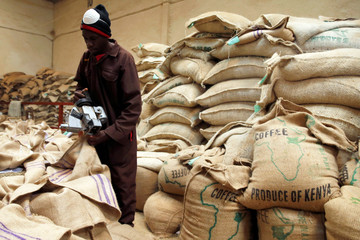 An employee closes coffee bags at the Central Kenya Coffee Mill near Nyeri