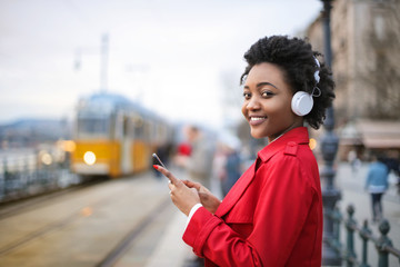 Girl listening music, while waiting for the train