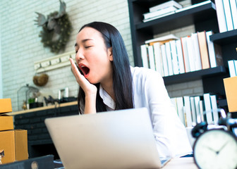 businesswoman yawn sleepy in working time at home office with laptop and clock, light process style