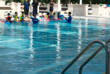 Swimming pool stair on blur photo kids practice swimming with trainer on background