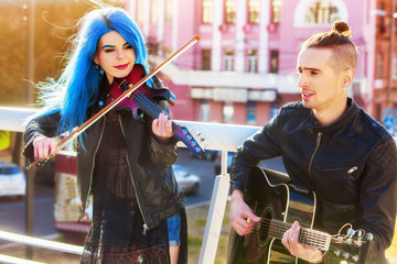 Playing viola woman and man perform music on violin and guitar in city outdoor. Girl with blue hairstyle and eyebrows performing jazz on urban street. Good hobbies for people.
