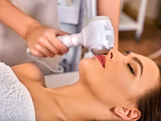 Ultrasonic facial treatment ultrasound face machine. Woman receiving electric lift massage spa salon. Electronic stimulation female muscles. Improvement of skin condition.