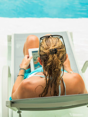 Woman using tablet computer while relaxing by the pool