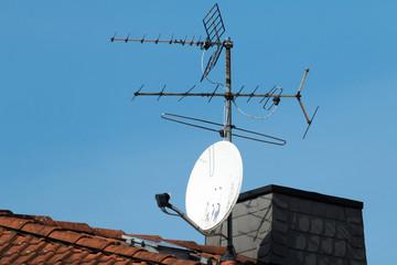 Satellitenschüssel und alte Antenne auf einem roten Dach Fototapete