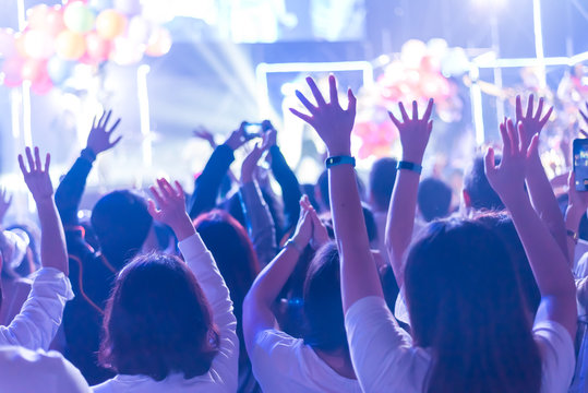 Crowd of hands up concert stage lights enjoying concert, and people fan audience silhouette raising hands in festival music rear view with spotlight glowing effect, blurred