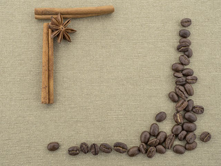 Packings of coffee beans, cinnamon sticks on rough canvas..Copy space.