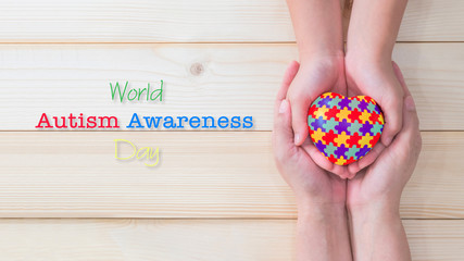 World Autism Awareness day, mental health care concept with puzzle or jigsaw pattern on heart with autistic child's hands supported by nursing family caregiver