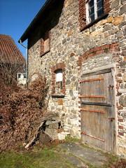 Verlassene alte Scheune aus Bruchstein mit schöner Holztür bei Sonnenschein in Heidenoldendorf bei Detmold im idyllischen Ostwestfalen-Lippe