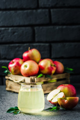 Cinnamon apple kombucha and fresh apples in wooden box on concrete background. Selective focus, space for text.