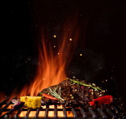 Aluminium Prints Grill / Barbecue Fiery grill grid with piece of beef steak and grilled vegetable.
