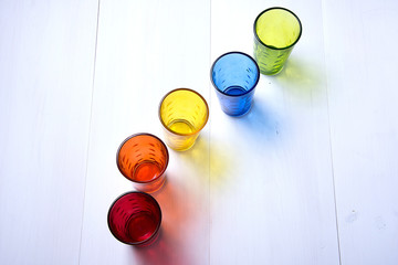five multicolored glass cups one after the other on white wooden background