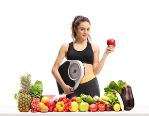 Fitness woman with a weight scale and an apple behind a table with fruit and vegetables