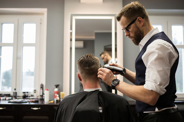 Focused barber having customer hair