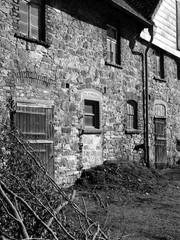 Schöne alte Fassade eines Bauernhaus aus Bruchstein im Sonnenschein in Heidenoldendorf bei Detmold im Kreis Lippe, fotografiert in klassischem Schwarzweiß