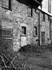 Alter Bauernhof mit Bruchsteinfassade und Holztüren mit Patina bei Sonnenschein in Heidenoldendorf bei Detmold im Lipperland, fotografiert in neorealistischem Schwarzweiß