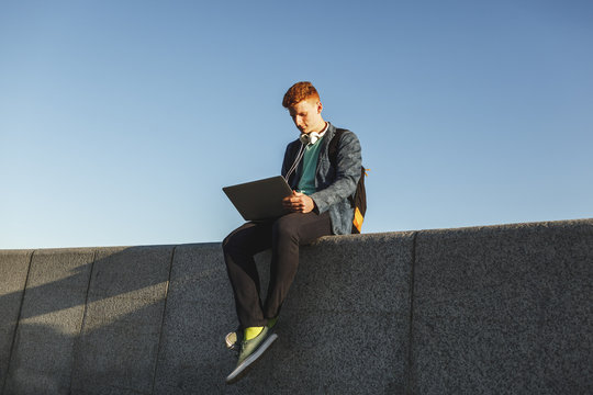 Redheaded young man sitting on wall using laptop