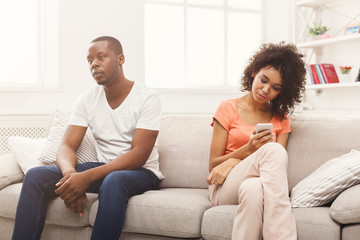 African-american couple at home, girl texting