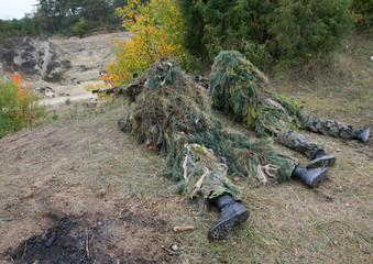 Two camouflage hunters or soldiers hiding in bushes in camouflage autumn background. Sniper with rifle.