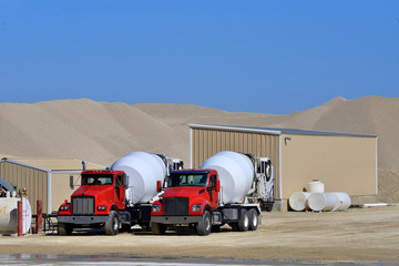 two cement mixer trucks waiting to be loaded