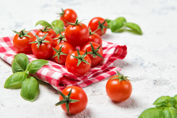Fresh cherry tomatoes with basil leaves on a stone table with red checkered towel, healthy food