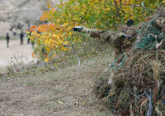 Camouflage Hunter or soldier aiming hiding in bushes in camouflage autumn  background. Sniper with rifle.