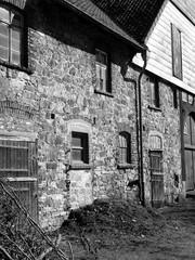 Bauernhaus mit Fassade aus Naturstein und alten Sprossenfenstern in Heidenoldendorf bei Detmold in Ostwestfalen-Lippe, fotografiert in neorealistischem Schwarzweiß