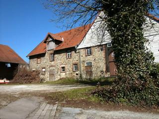 Alter Bauernhof mit Bruchsteinfassade vor blauem Himmel bei Sonnenschein in Heidenoldendorf bei Detmold im schönen Ostwestfalen-Lippe