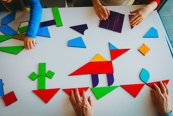 teacher and kids play with puzzle or tangram, education