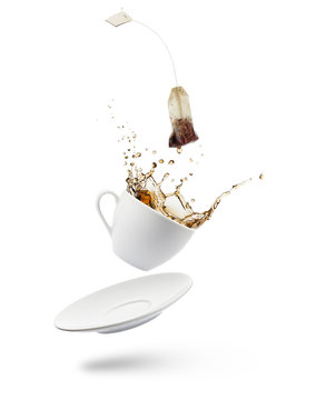 cup of tea falling with tea bag splashing on white background