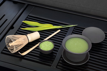 Japanese green matcha tea with powder and health drink in cup with whisk and stick stirrer with bamboo leaf on black tray.