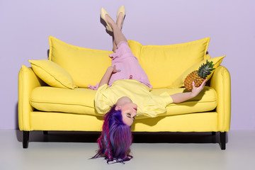 beautiful young woman lying upside down on yellow couch with pineapple