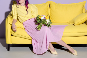 cropped shot of woman sitting on yellow couch with floral bouquet Wall mural
