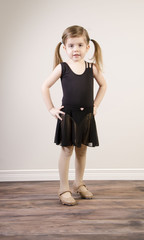 A young girl poses and practices tap dance on a wooden floor