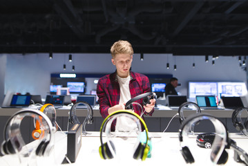 Photo sur Plexiglas Magasin de musique Young man looks at headphones in the electronics store Choosing and buying headphones in a technology store.