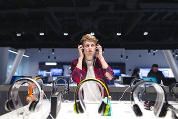 The buyer evaluates the sound of the headphones. A young, handsome man listens to music in a modern technology store. Select and buy headphones in the store