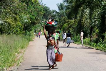 An internally displaced Congolese woman carries her belongings as she walks to the market in Kaniki-Kapangu village near Mwene Ditu in Kasai Oriental Province