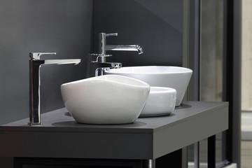 Trzy umywalki z nowoczesnymi kranami na szarej szafce w łazience i w sklepie.