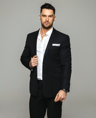 Handsome man wear black suit and white shirt posing over grey background