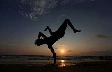A b-boy is seen in silhouette as he performs on a beach as the sun sets in Colombo