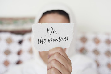 woman with a hijab and the text we the women
