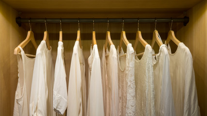 Picture taken straight into a wardrobe with lighting. White summer blouses and sweaters on hangers.