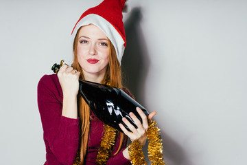 beautiful red-haired girl celebrating New Year and Christmas, wearing a red cap on her head, holding a bottle of champagne in her hands
