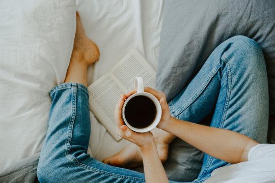 junge Frau mit Tee im Bett