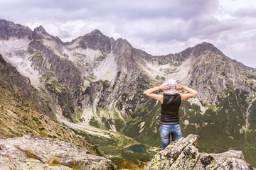 Górskie krajobrazy w Słowackich Tatrach. Kobieta obserwująca ze szczytu, górską dolinę.