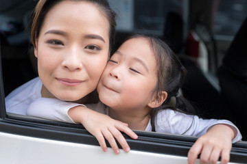 Happy woman with little child driving in car.