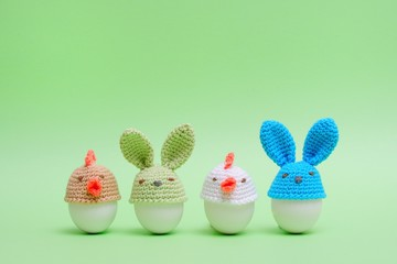 Easter holiday concept with cute handmade eggs, bunny, chicks on green background. Easter ideas