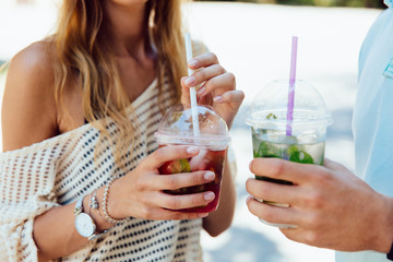 Close-up view of couple holding fresh cocktails, outdoors