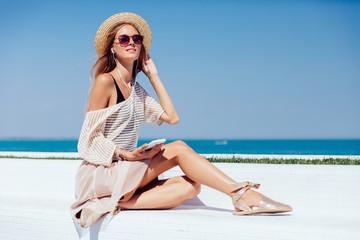 Beautiful woman in headphones sitting on bench, near the sea