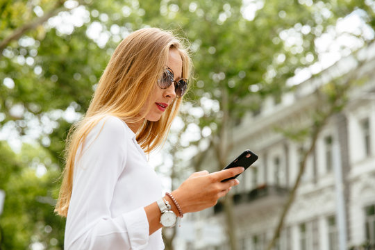 Stylish woman in sunglasses with smartphone outside