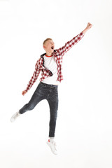 Full length picture of content youngster 18y wearing plaid shirt yelling and acting like superhero lifting hand upward, isolated over white background